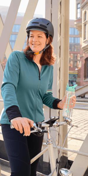 Sportlich gekleidete Frau steht lächelnd an ihrem Fahrrad