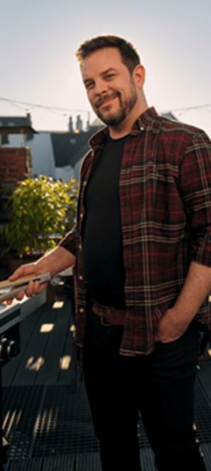 Un homme aux cheveux courts et à la barbe se tient devant un gril avec une pince à barbecue.