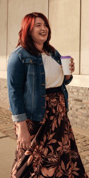 Une jeune femme aux cheveux roux et à la jupe longue tient une tasse à café à la main.
