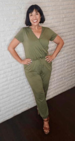 WW member Elsa, a woman with short brown hair with bands, wearing a green jumpsuit.