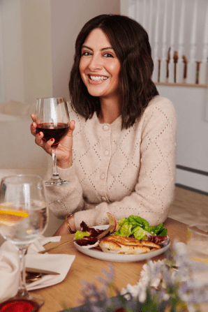 WW member Shannon, a woman with short brown hair wearing a cardigan enjoys a glass of wine with a meal