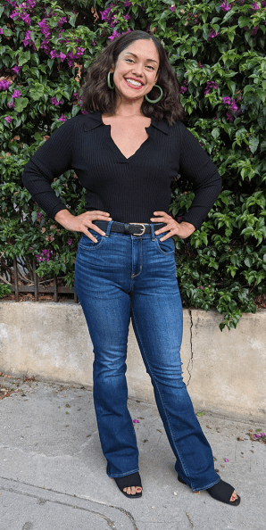 WW member Cassandra, a woman with short brown hair wearing a black top and blue jeans is outside in front of purple flowers