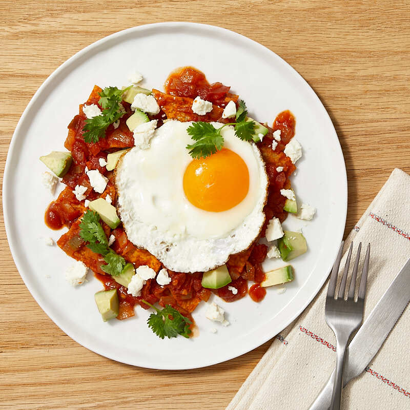Photo of Chilaquiles with fried eggs, cheese, and avocado by WW