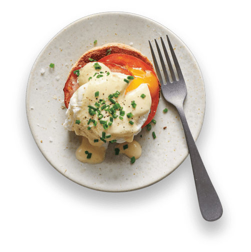Poached eggs with hollandaise and bacon on a plate
