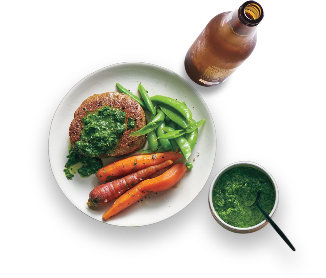 Filets mignons with fresh herb sauce and a light beer on a plate. Drink bottle and side of green herb sauce.
