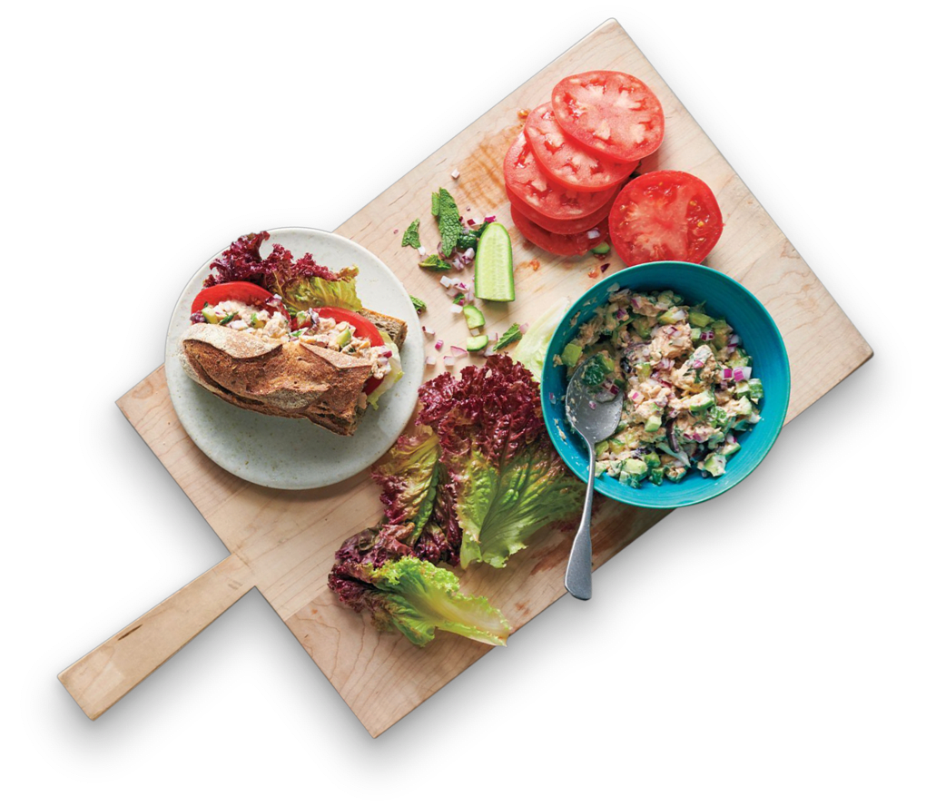 Salmon, cucumber, and mint sandwich and ingredients on a cutting board