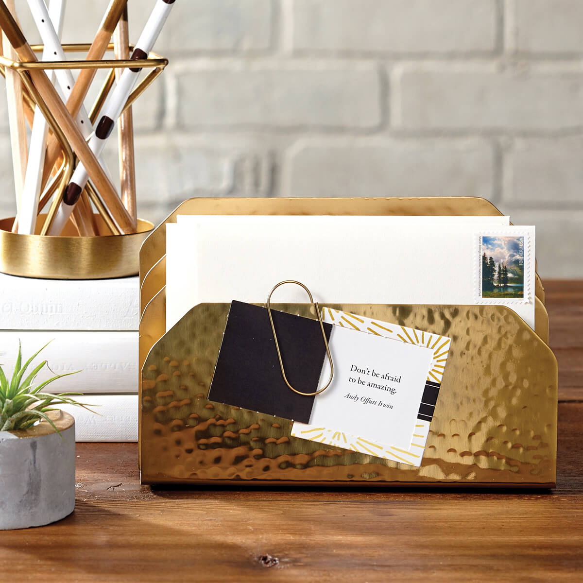On a wooden table sits a golden holder with letters and a paperclip holding a card on it. A small plant add some green to the image and a pencil holder sits on a small ledge on the back left of the photo, in front of a gray brick wall.