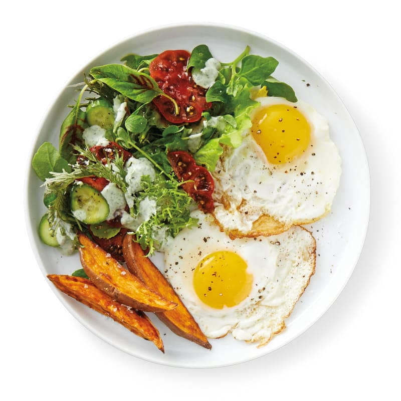 Photo of Fried eggs with roasted sweet potato wedges and mixed greens by WW
