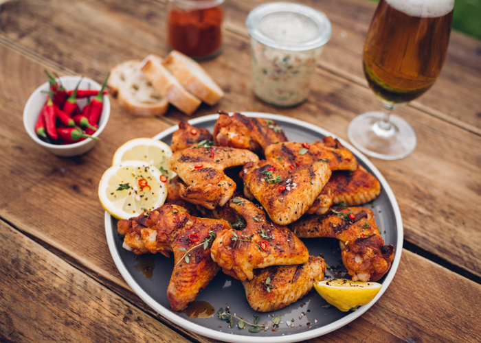 Spicy chicken wings on a picnic table with beer