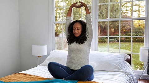 Mulher negra sentada com as pernas cruzadas em cima da cama fazendo um alongamento com os braços para cima
