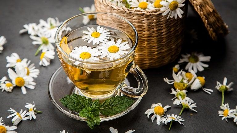 Xícara de vidro com chá dentro em cima de uma mesa preta com flores de mini margarida enfeitando em volta
