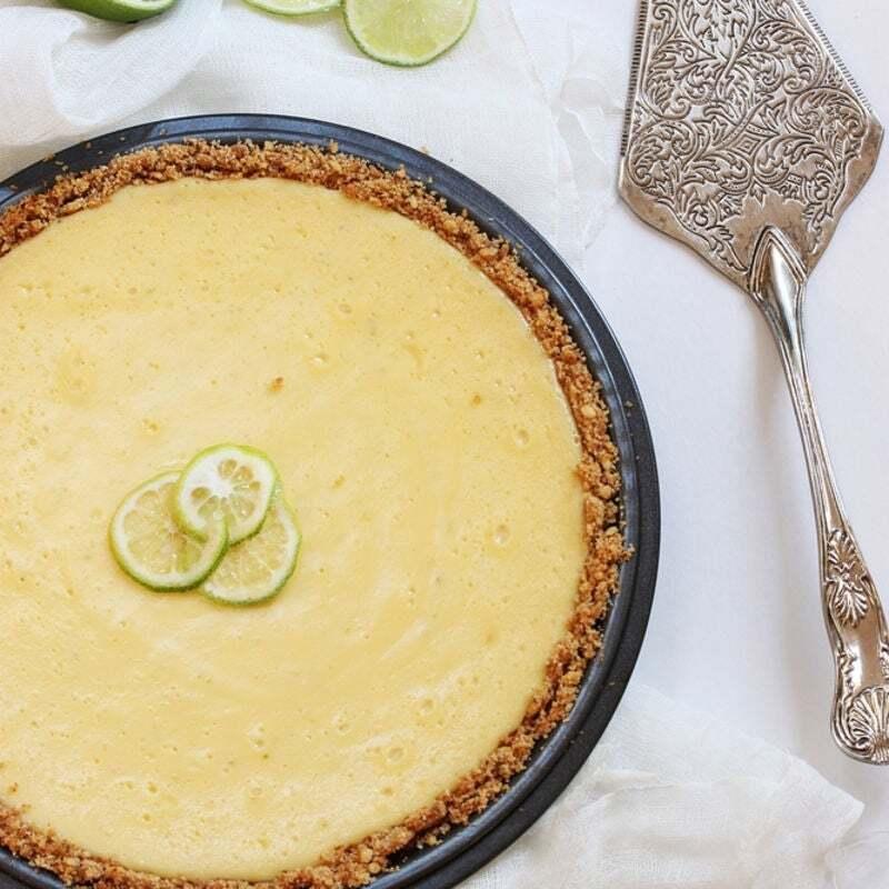 torta de limão dentro de um prato redondo em cima de uma mesa com toalha branca e uma espátula de corte ao lado
