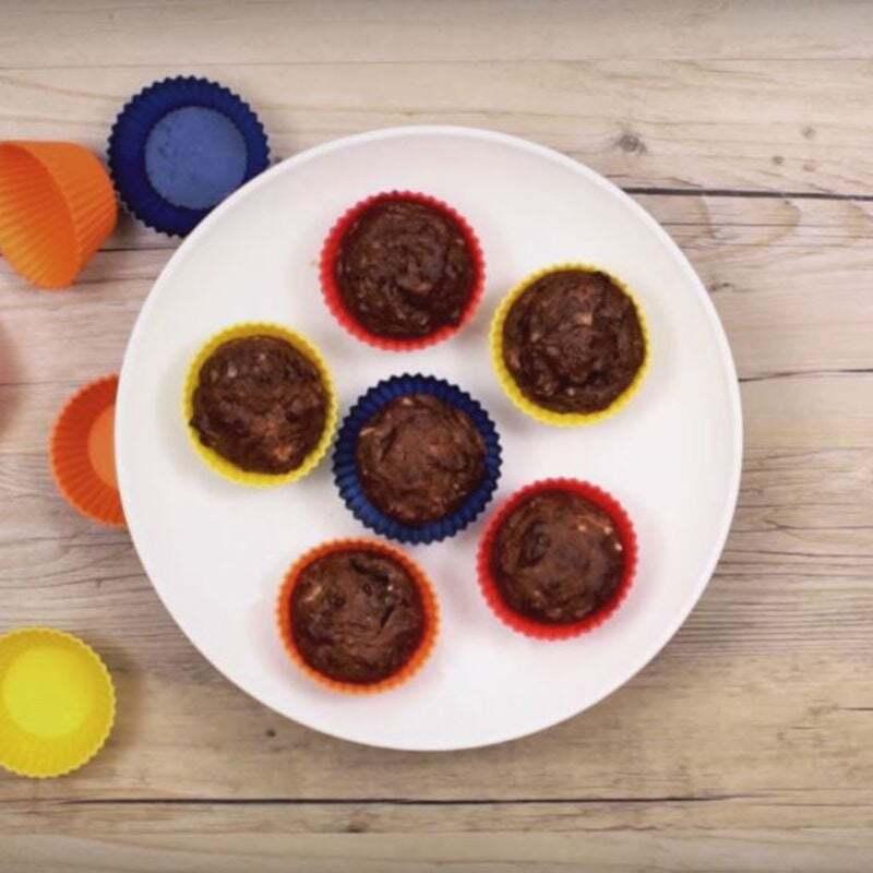 Seis cupcakes de chocolate dentro de um prato branco em cima de uma mesa de madeira com formas de papel colorido ao lado