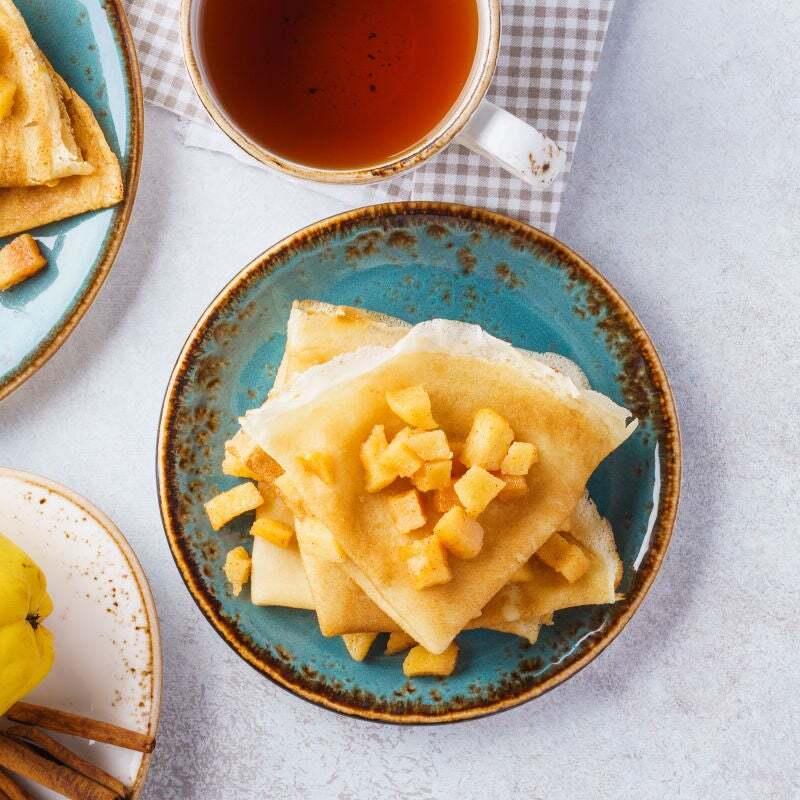 Crepe dobrado em triângulo com maçã picada em cubos e canela dentro de um prato redondo azul em cima de uma mesa branca. Ao lado há uma xicara de chá