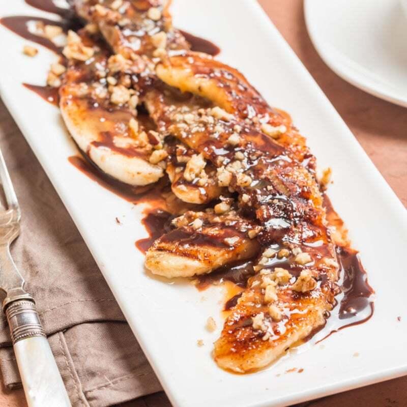 bananas assadas com nozes e chocolate derretido por cima em um prato retangular branco ao lado há um garfo e um guardanapo de pano cinza