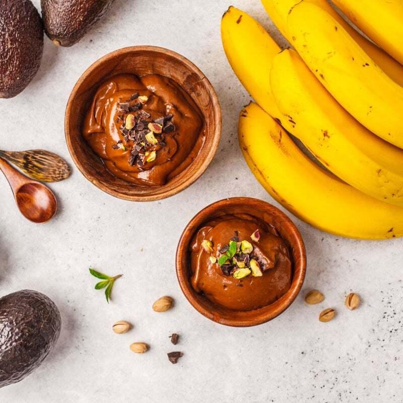 Duas tigelas redondas de bambu com mousse de chocolate com pistache e raspas de chocolate por cima. Abacates e bananas ao lado enfeitando a mesa