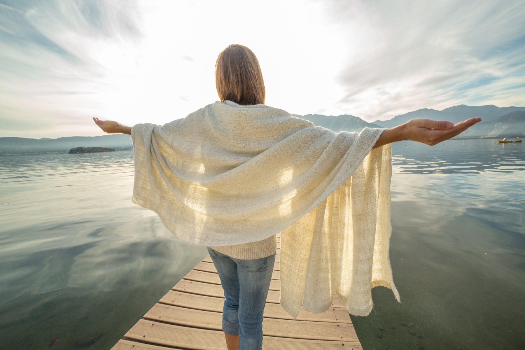Mulher à beira de um lago de braços abertos agradecendo ao sol.
