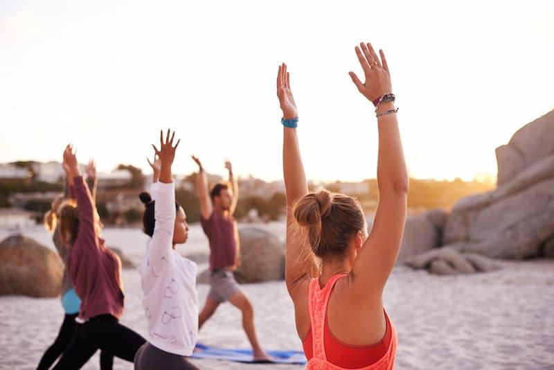 Cinco pessoas fazendo Yoga na praia