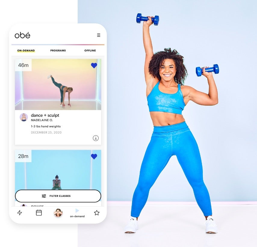 Screenshot of available fitness classes in Obé app. Woman standing with dumbbell in right hand raised overhead and dumbbell in left hand just above shoulder.