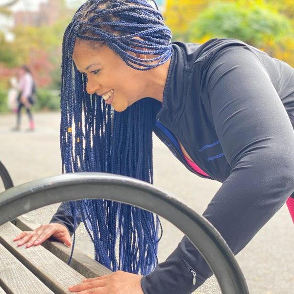 Frau mit Rastazöpfeln macht Liegestütze an einer Parkbank