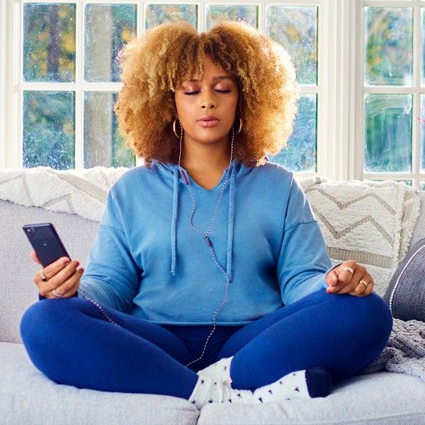 Junge Frau mit Afrofrisur sitzt meditierend in gemütlicher Kleidung auf dem Sofa