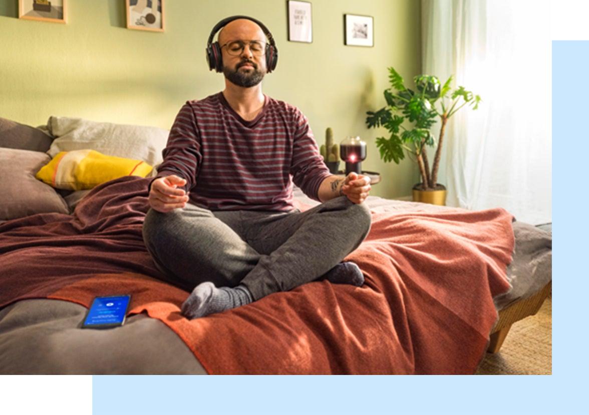 Un homme assis en tailleur sur un lit avec des écouteurs