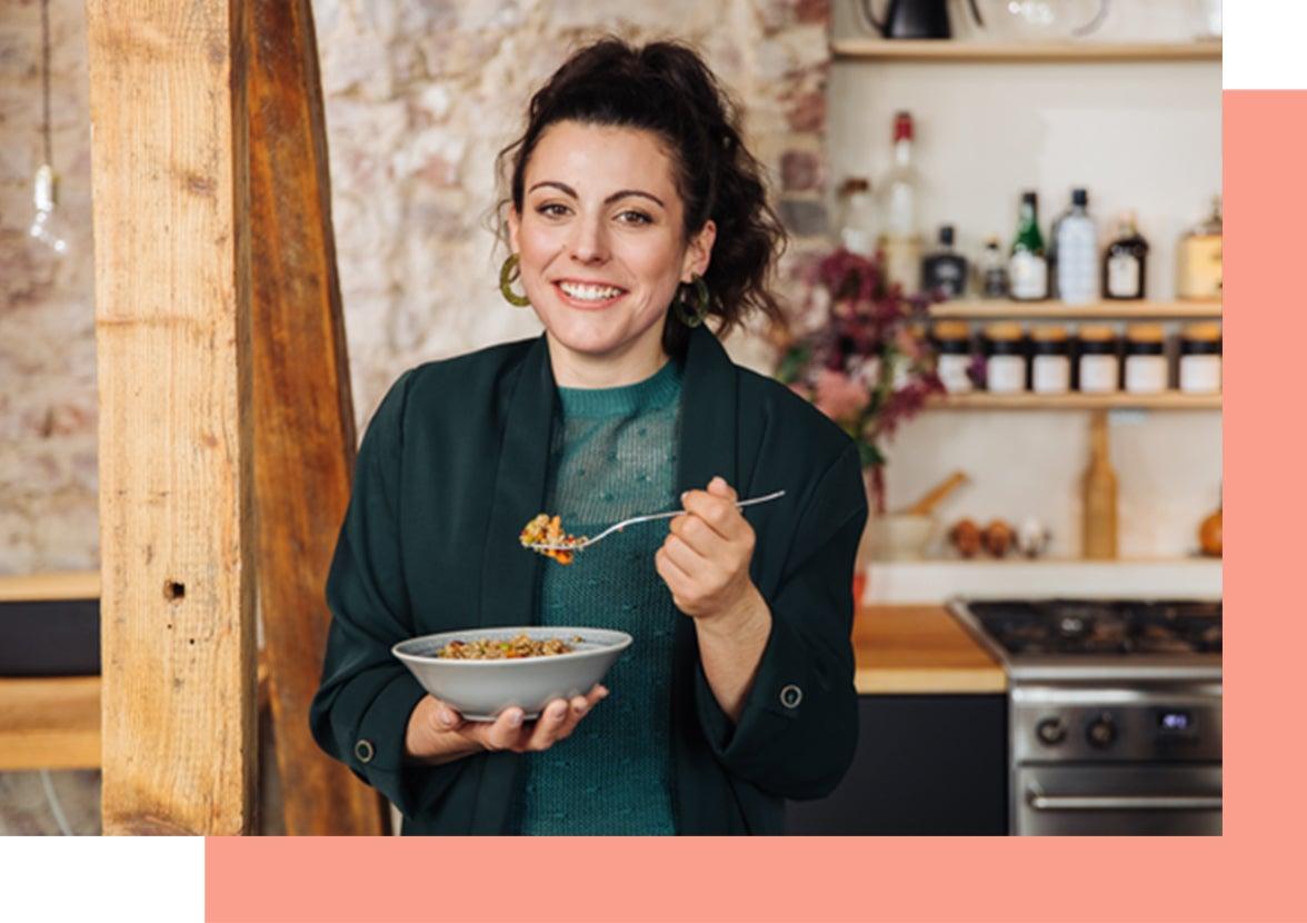 WW Mitglied in einer Küche mit einer Schale mit Essen lacht in die Kamera