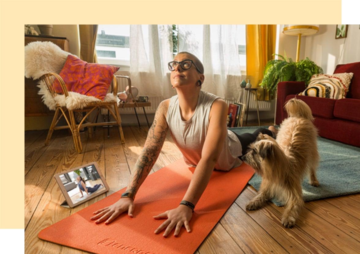Junge Frau macht mit ihrem Hund daneben ein Yoga Workout