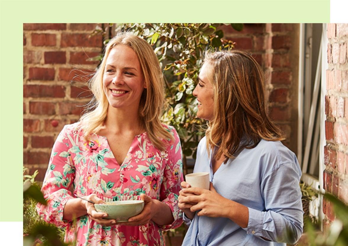 Zwei junge blonde Frauen stehen lachend in einem Innenhof