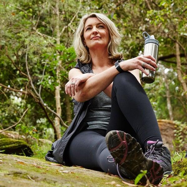 Blonde Frau sitzt in Sportkleidung auf einem Waldboden