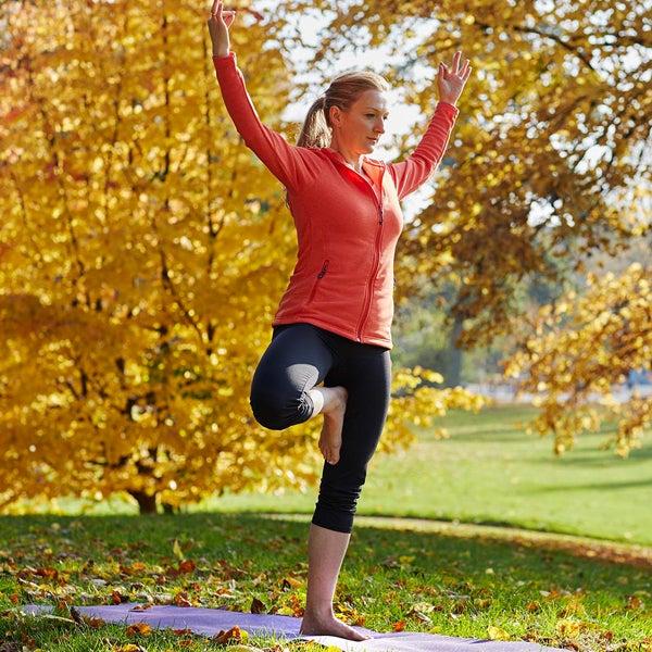 Blonde Frau steht auf einer Wiese und macht Yoga