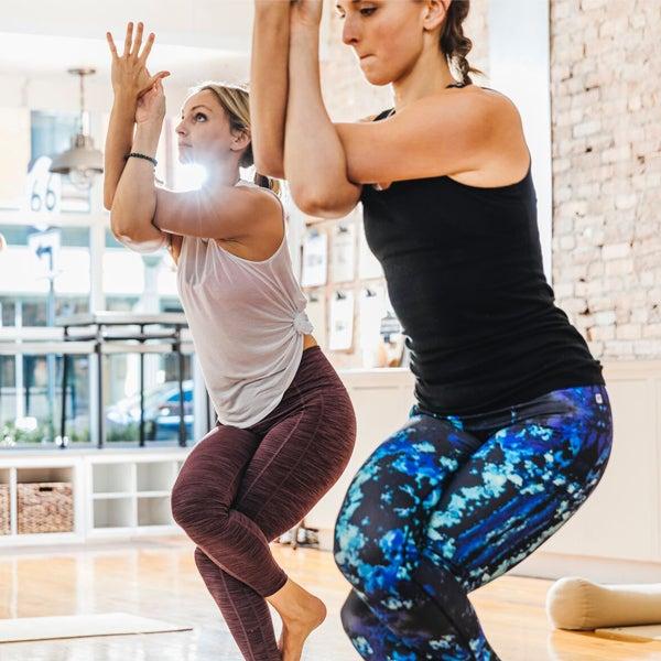 Zwei Frauen in Sportkleidung machen eine Pilates-Übung