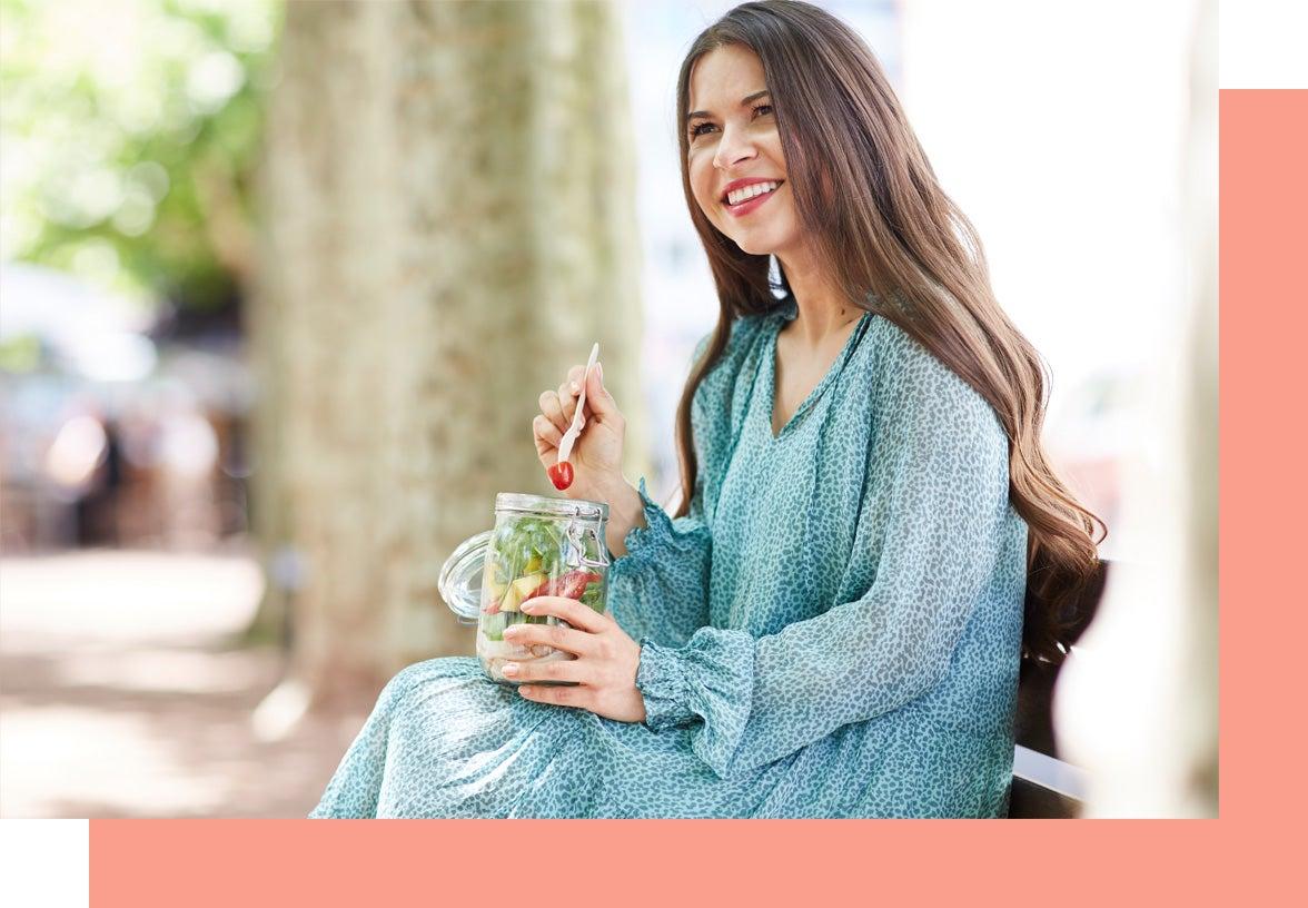 Une membre WW assise sur un banc qui mange une salade