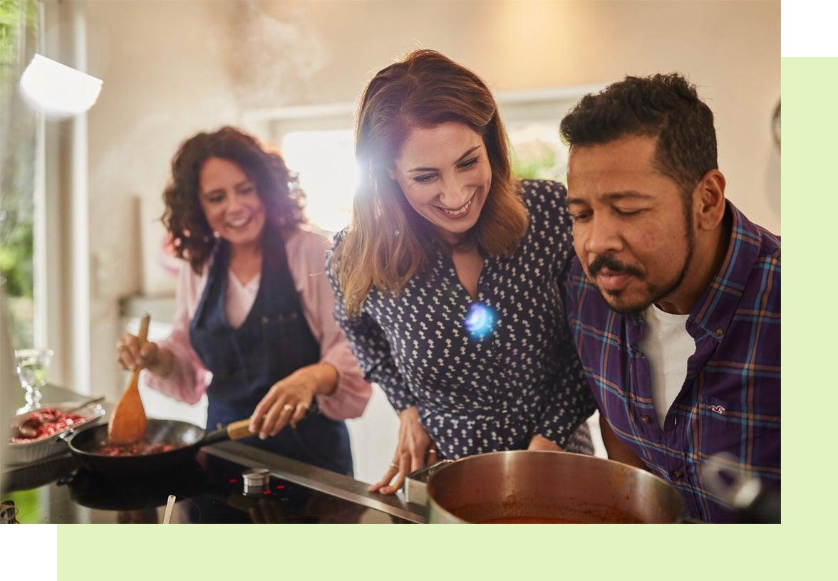 Deux femmes aux cheveux bruns et un homme aux cheveux noirs et à la peau foncée font la cuisine