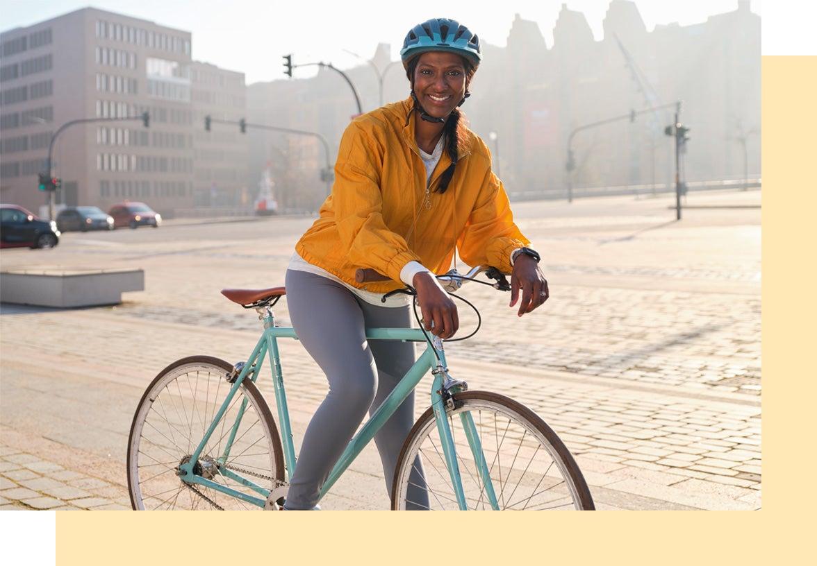 Junge Frau mit dunkler Haut auf ihrem Fahrrad