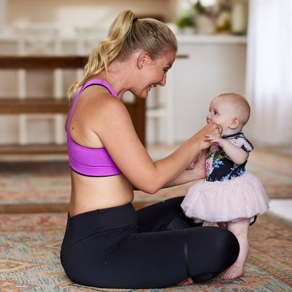 Blonde Frau in Sportkleidung lacht ihr Baby an