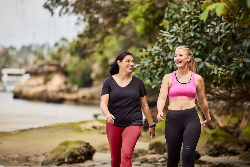 Duas mulheres com roupa de ginástica caminhando na beira da praia