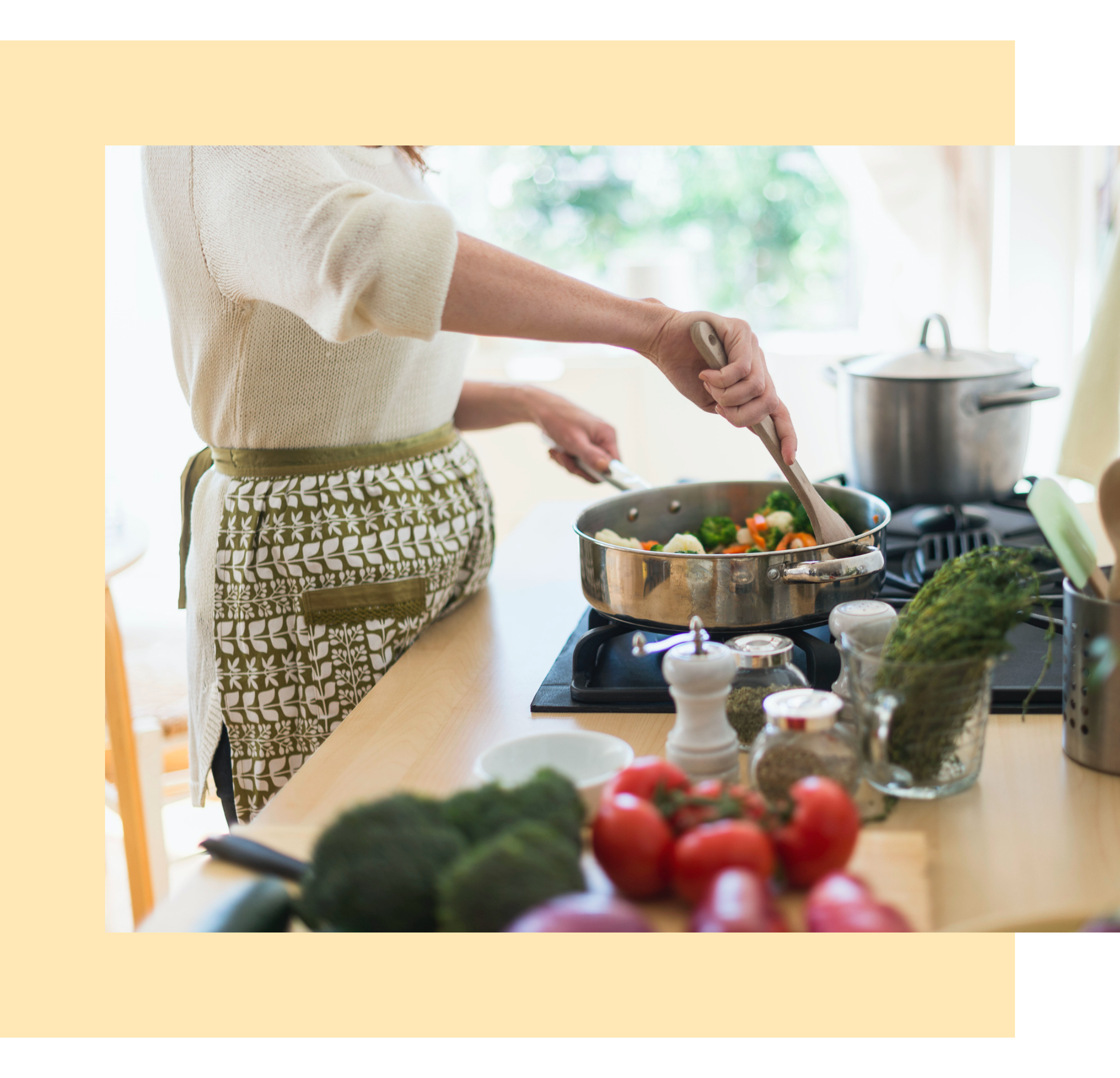 A woman is preparing a pan full of veggies in a kitchen.