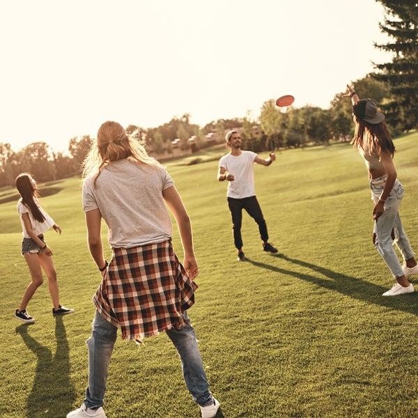 Junge Leute spielen draußen Frisbee