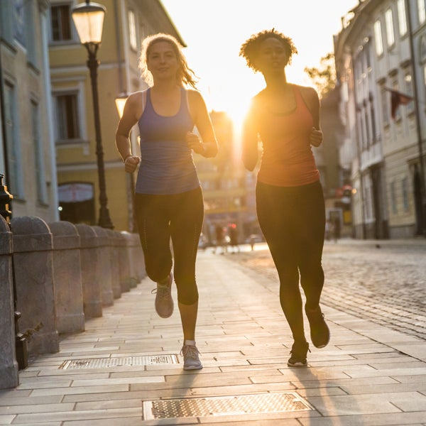Zwei junge Frauen joggen auf einer Straße