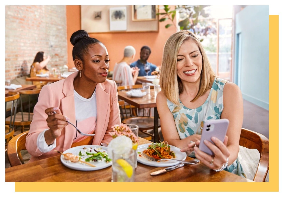 Two women eat a meal while looking at one of the women's phone.