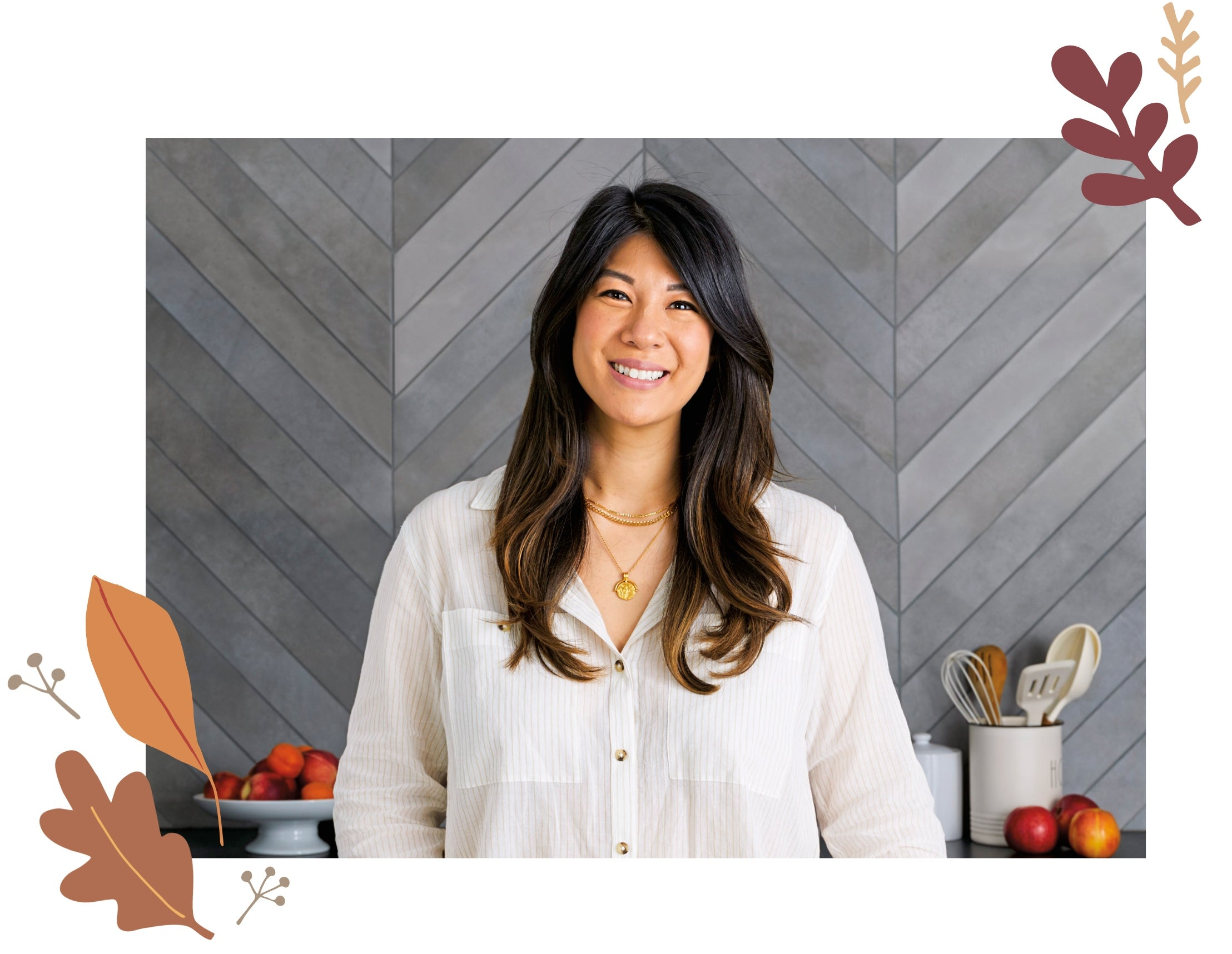 WW Food Director Sherry Rujikarn, wearing a white shirt, standing in front of a gray wall with a plate of fruit and a jar of kitchen tools.