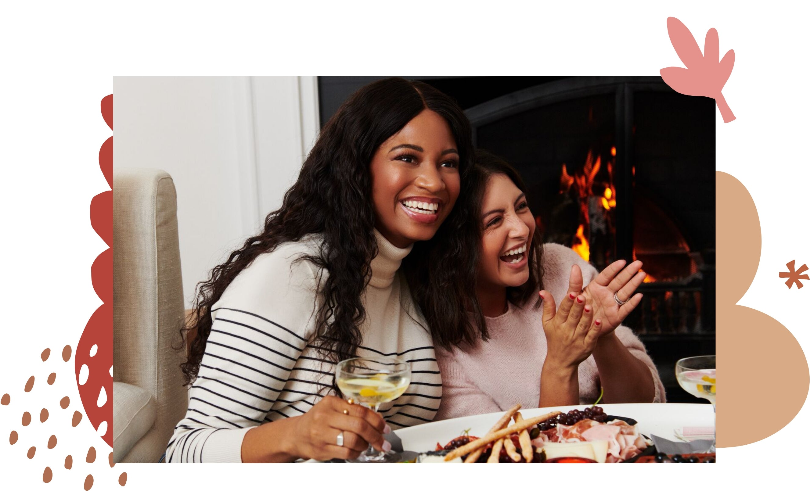 Two women, one in a white stripped shirt and another in a pink sweater, are smiling and enjoying a meal and drinks.