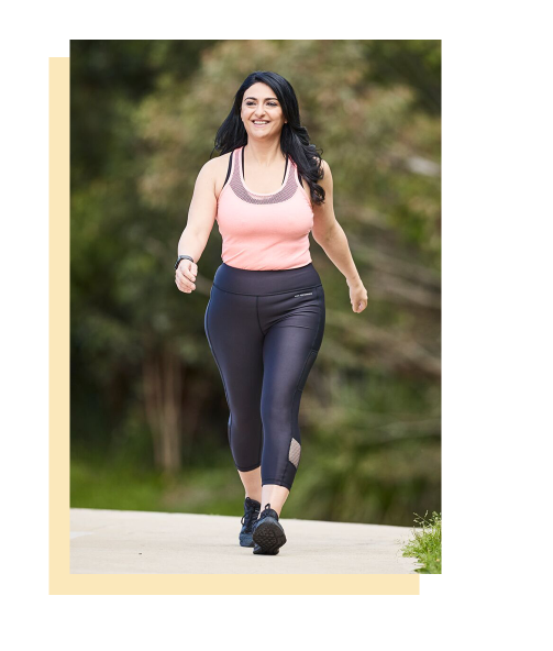 A smiling woman is walking along a path in a park while wearing black pants and sneakers and a pink tank top. Her black hair is cascading over her shoulders.
