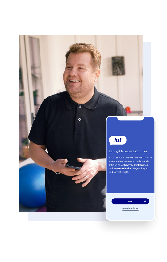 James Corden stands smiling with a phone in his hand.
