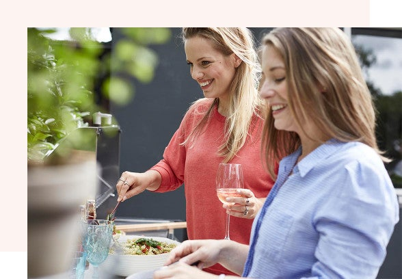 A man and a woman are clinking glasses of red wine together over an outdoor dinner table. They are smiling at each other.
