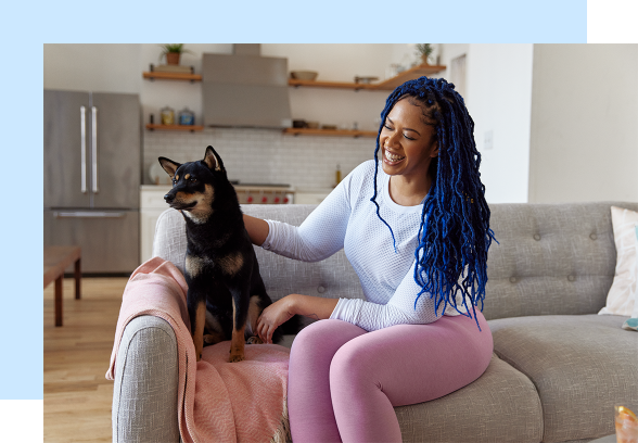 A black woman with blue hair is laughing on a couch while petting a medium-sized black and brown dog.