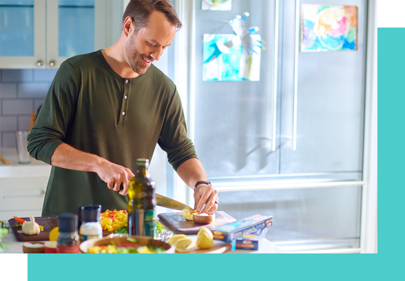 A white man with brown hair and a green shirt preparing a meal, cutting fruits and vegetables..