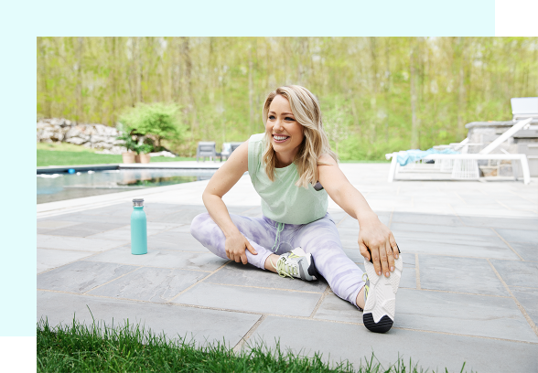 A woman with blonde hair smiles outdoors by the pool while stretching, holding her hand to her foot.