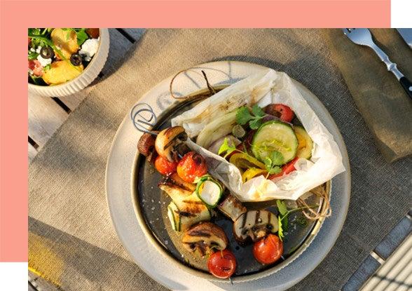 Teller mit Gemüsepäckchen und gegrillten Gemüsespießen
